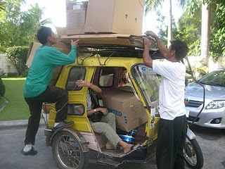 Imelda (cauayan mission home house keeper), Ronnie (home groundskeeper), & Ronnie (Church facilities group ) making good use of Sis Carlos' boxes. Off to sell them.
